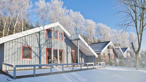 Blaues Ferienhaus im Schnee - Ferienpark Mirow